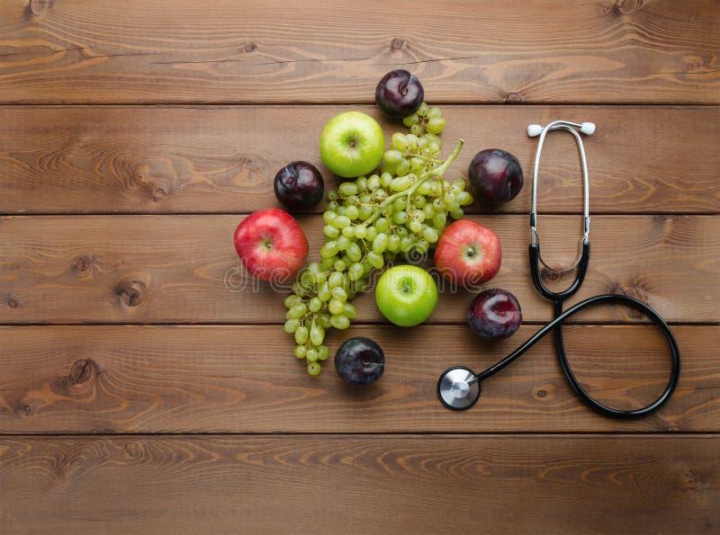 Concept de régime avec le stéthoscope et les fruits frais médicaux image stock