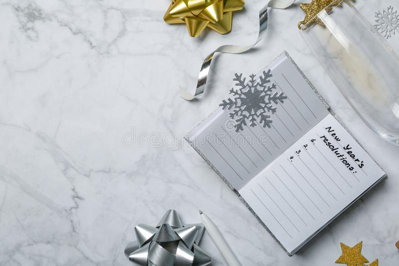 Concept de résolutions de nouvelle année - carnet avec la liste de buts et de décorations argentées d'or photographie stock