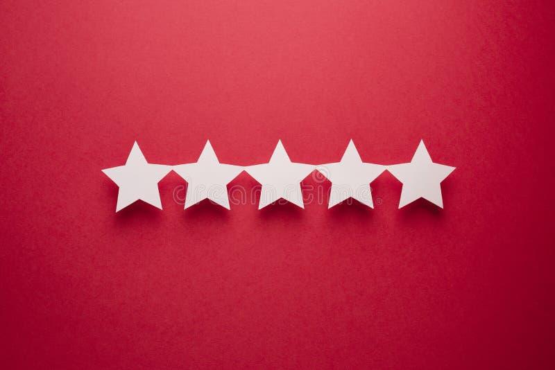 Concept de r?troaction Cinq étoiles de livre blanc d'approbation sur un fond rouge images stock