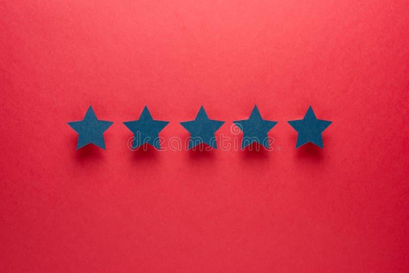 Concept de r?troaction Cinq étoiles de papier bleues d'approbation sur un fond rouge photo stock