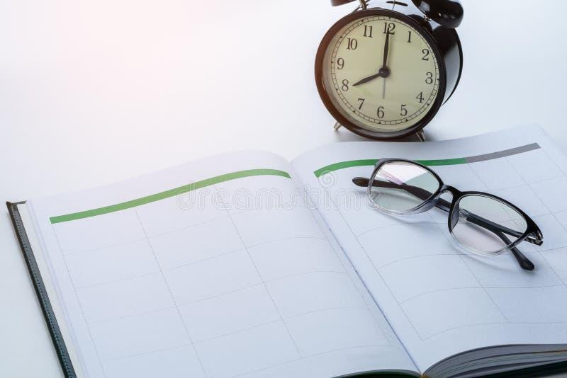Concept de rappel d'affaires avec le livre de rendez-vous, réveil, gl images stock