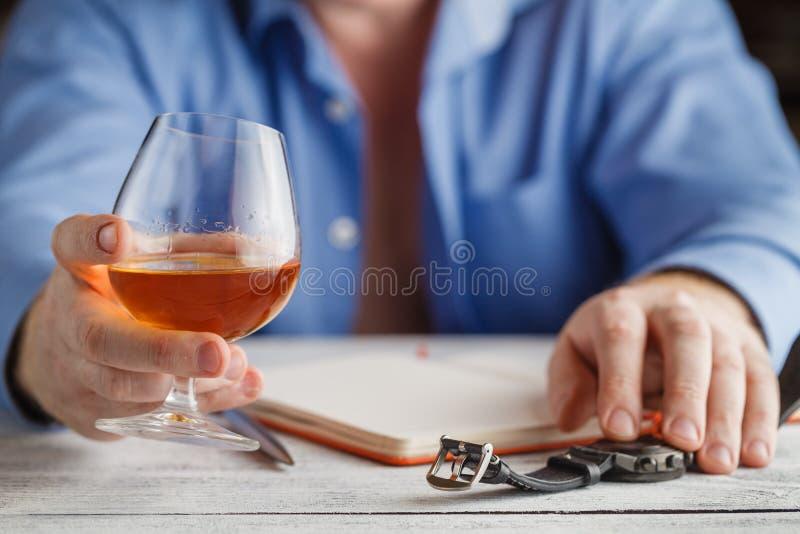 Concept de relaxation - un verre d'eau-de-vie fine dans des mains masculines sélecteur photos libres de droits