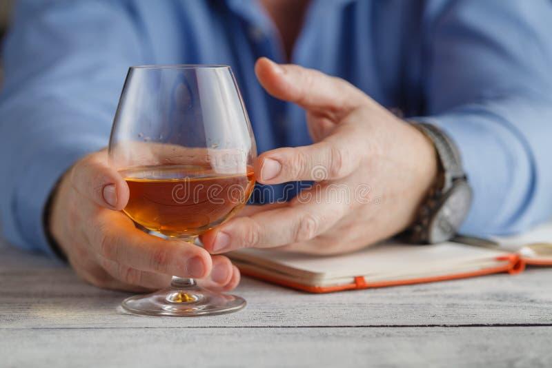 Concept de relaxation - un verre d'eau-de-vie fine dans des mains masculines sélecteur photographie stock libre de droits