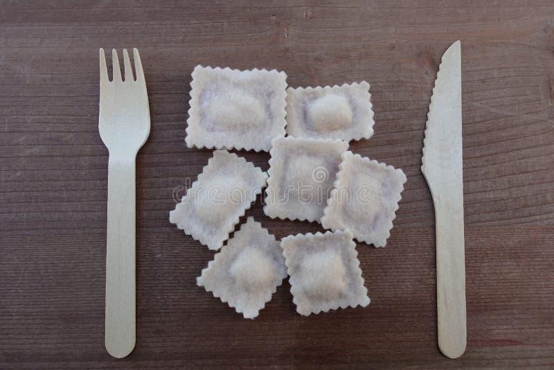 Concept de repas avec le plat italien des ravioli, des pâtes remplies, de la conception de tissu et des couverts en bois image stock