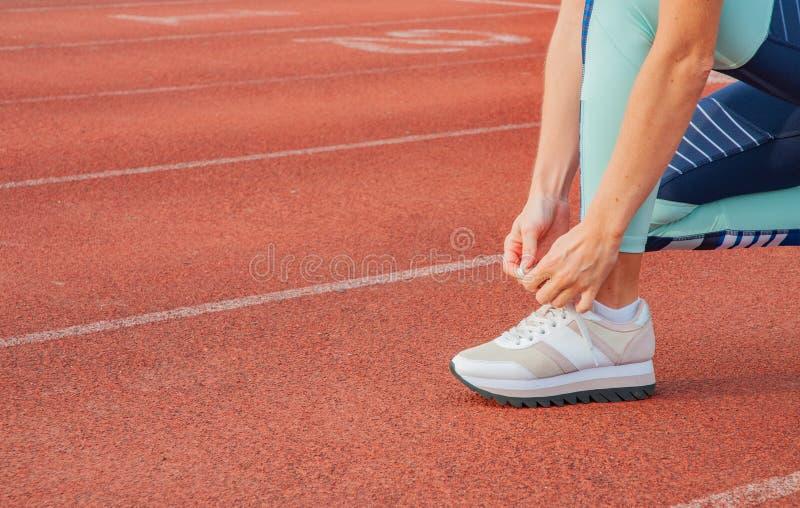 Concept de séance d'entraînement Coureur de femme de sports attachant des dentelles image stock