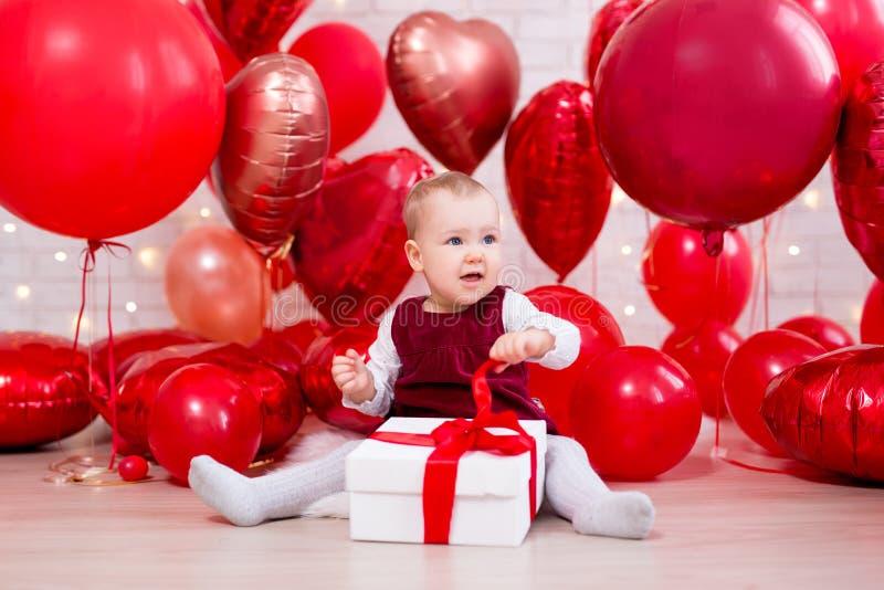 Concept de Saint-Valentin - petit boîte-cadeau mignon d'ouverture de bébé au-dessus de fond rouge de ballons images stock