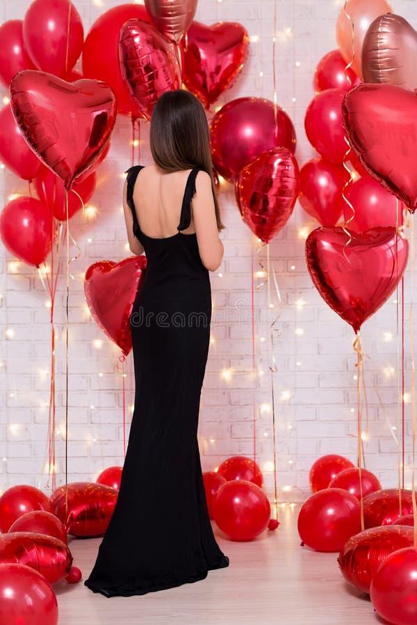 Concept de Saint-Valentin - vue arrière de belle femme dans la longue robe noire avec les ballons en forme de coeur images libres de droits