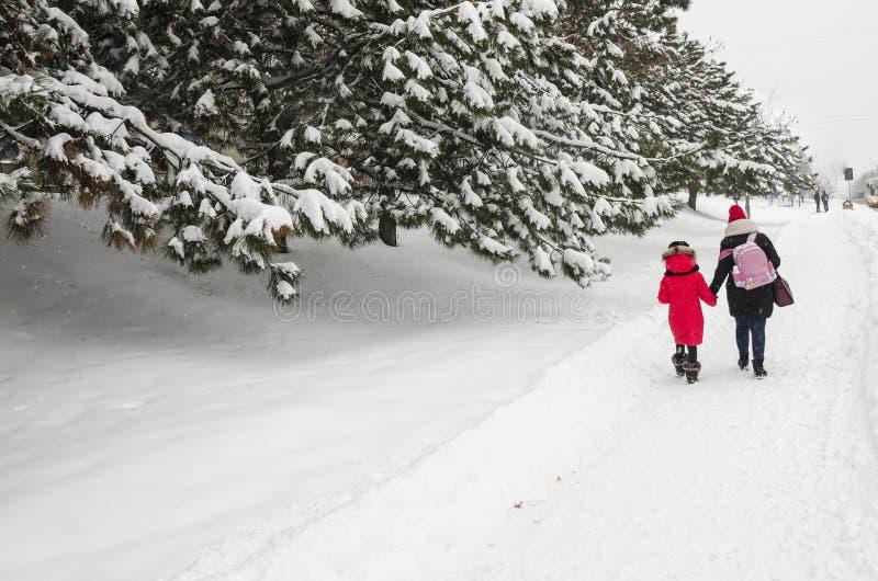 Concept de saison d'hiver Une maman avec sa fille marchent à la maison de l'école avec un sac à dos rose Promenade gentille de fa photos stock