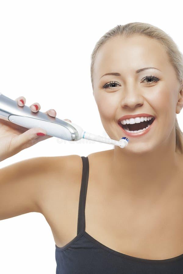 Concept de santé dentaire : Femme caucasienne blonde balayant sa pièce en t images stock