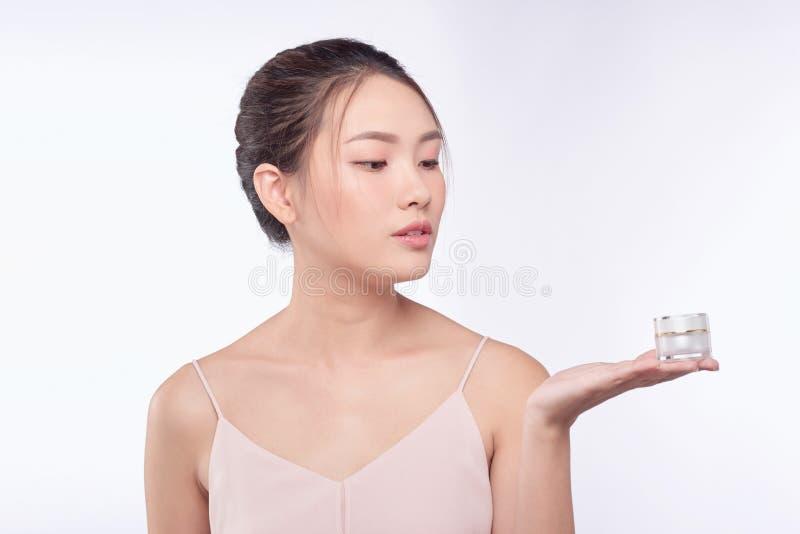 Concept de santé et de beauté - femme asiatique attirante appliquant la crème sur sa peau images libres de droits