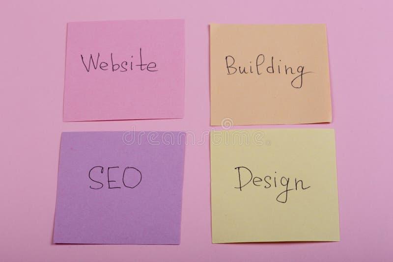 concept de seo - les notes collantes colorées avec des mots conçoivent, site Web, le seo, bâtiment sur le fond rose image stock