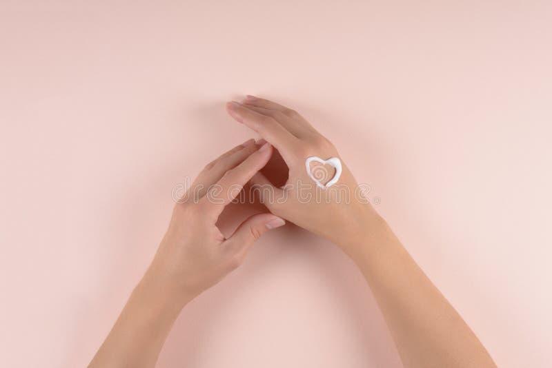 Concept de soin de peau Femme appliquant la crème de main sur le fond gonflé Configuration plate Vue supérieure images stock