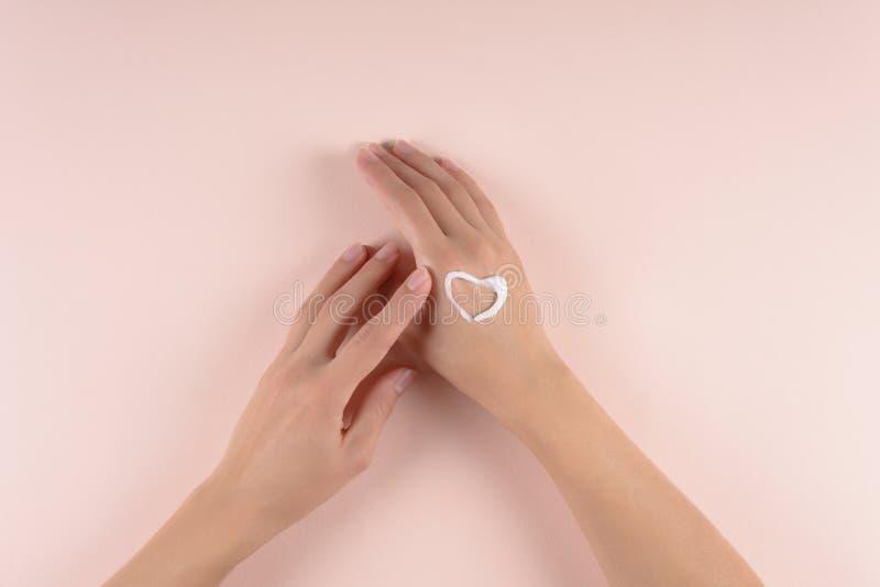 Concept de soin de peau Femme appliquant la crème de main sur le fond gonflé Configuration plate Vue supérieure photo libre de droits