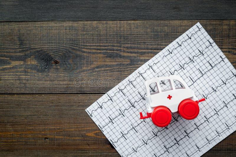 Concept de soins d'urgence Jouet de véhicule d'ambulance près de cardiogramme sur l'espace en bois foncé de vue supérieure de fon image libre de droits