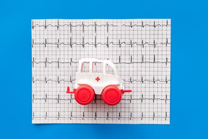 Concept de soins d'urgence Jouet de véhicule d'ambulance près de cardiogramme sur la vue supérieure de fond bleu images stock