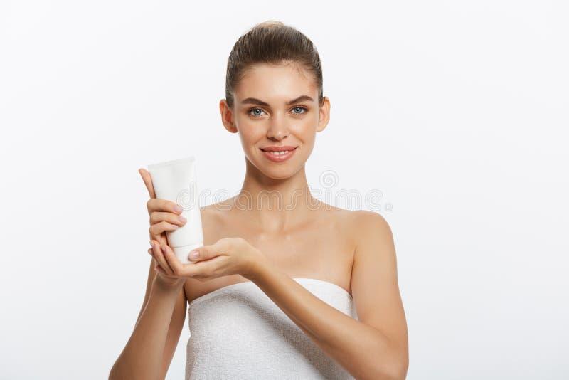 Concept de soins de la peau de la jeunesse de beauté - beau portrait caucasien de visage de femme tenant et présentant le produit photographie stock libre de droits