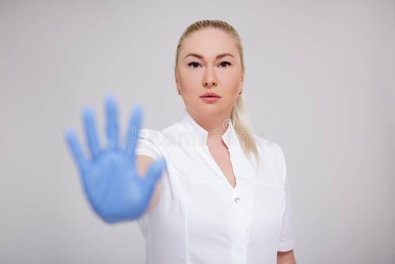 Concept de soins de santé et de pandémie du virus de la corona - attrayante femme médecin en uniforme blanc et gants bleus montra image stock
