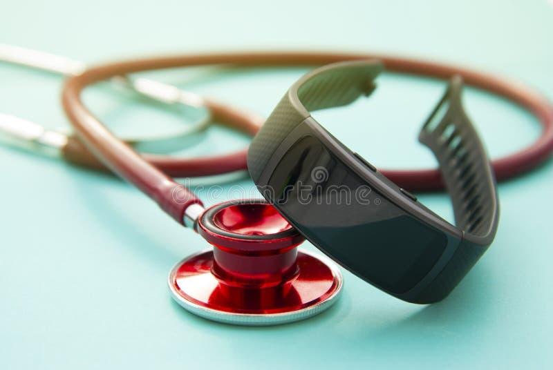 Concept de soins de santé Traqueur et sthetoscop d'activité de montre de forme physique au-dessus de fond bleu plan rapproché, fo photo stock