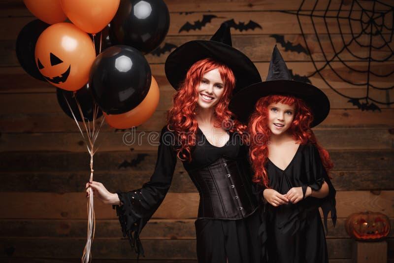 Concept de sorcière de Halloween - mère gaie et sa fille dans des costumes de sorcière célébrant Halloween posant avec du Ba oran photo stock