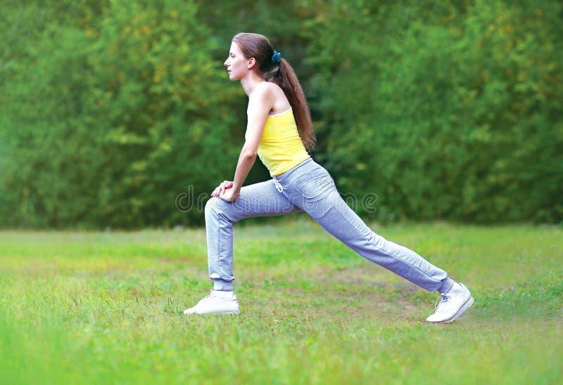 Concept de sport, de forme physique et de yoga - le sportif de femme fait étirant des exercices sur l'herbe images stock