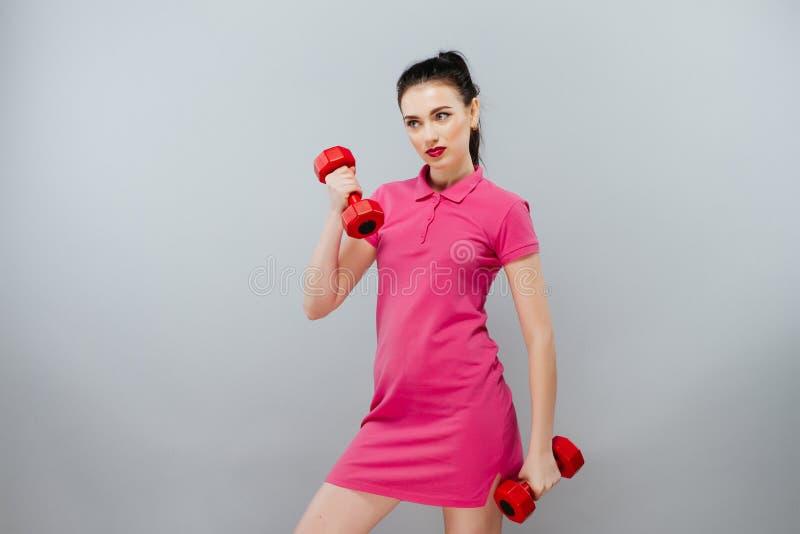 Concept de sport et de récréation - mains sportives de femme avec les haltères rouge-clair Jolie fille dans le sport image stock