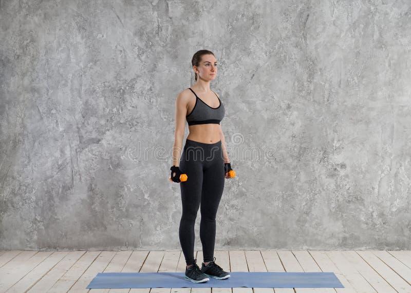 Concept de sport, de forme physique, de formation et de bonheur - mains sportives de femme avec les haltères rouge-clair images stock