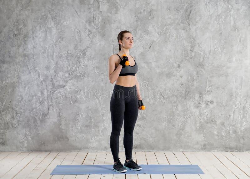Concept de sport, de forme physique, de formation et de bonheur - mains sportives de femme avec les haltères rouge-clair image stock