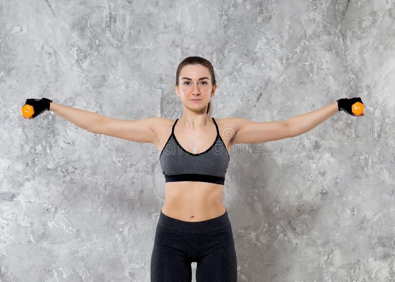 Concept de sport, de forme physique, de formation et de bonheur - mains sportives de femme avec les haltères rouge-clair photo libre de droits