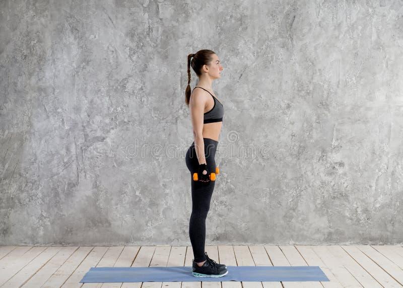 Concept de sport, de forme physique, de formation et de bonheur - mains sportives de femme avec les haltères rouge-clair photographie stock libre de droits