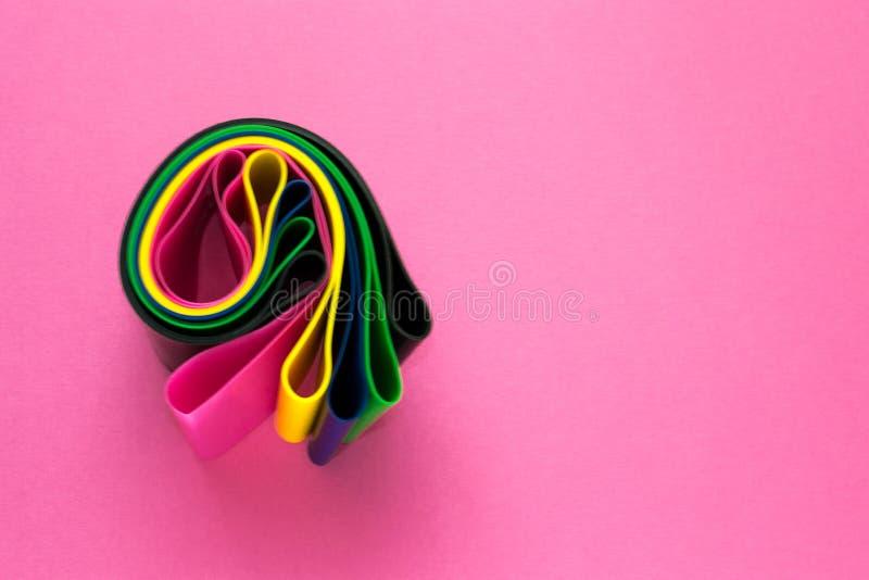 Concept de sport - a roulé l'ensemble d'extenseurs élastiques de forme physique colorée pour la femme sur le fond rose Mode de vi photos stock
