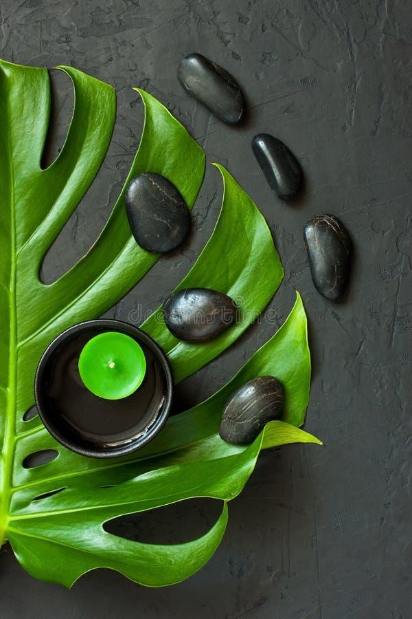Concept de station thermale - bougies, pierres et feuille verte sur la surface foncée photos stock