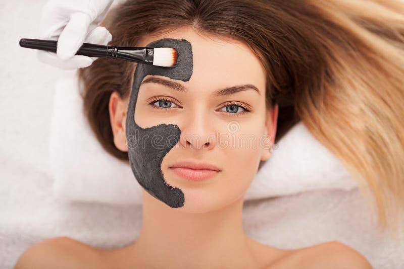 Concept de station thermale Jeune femme avec le masque facial nutritif dans le sel de beauté photos libres de droits