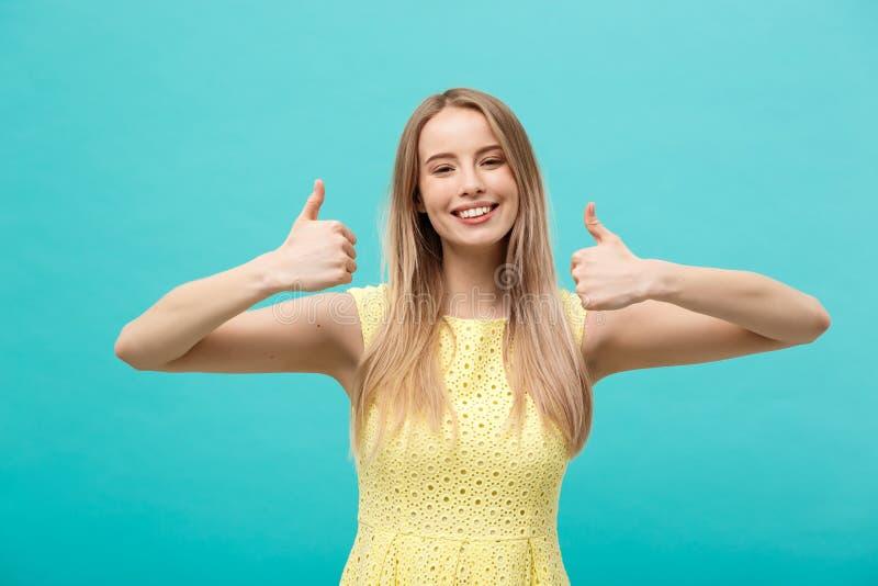 Concept de succès et de mode de vie : Jeune femme gaie heureuse montrant le pouce au-dessus du fond bleu en pastel photographie stock libre de droits