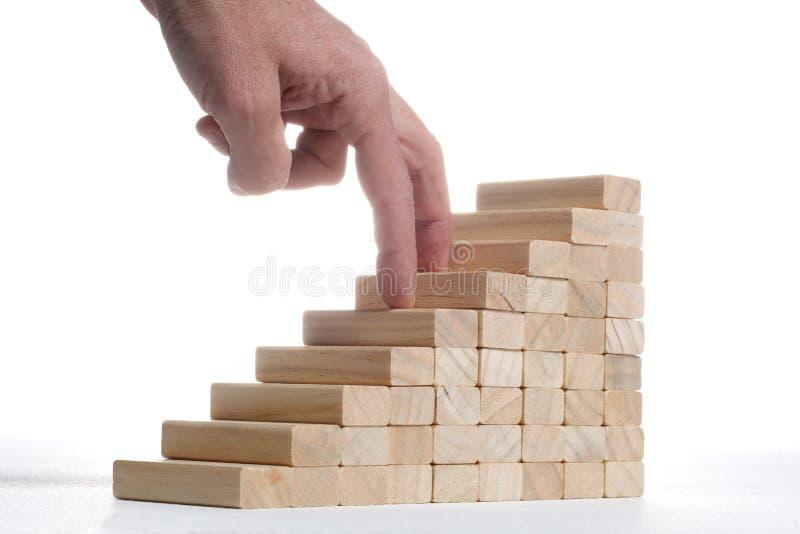 Concept de succès : les escaliers construisent avec les blocs en bois de jouet et le doigt deux humain le montant sur le fond bla images stock