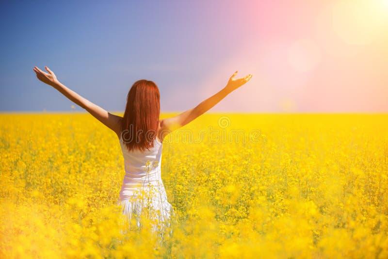 Concept de succ?s de libert? de personnes Femme heureuse dans le domaine avec des fleurs au jour ensoleill? dans la campagne Fond photographie stock libre de droits