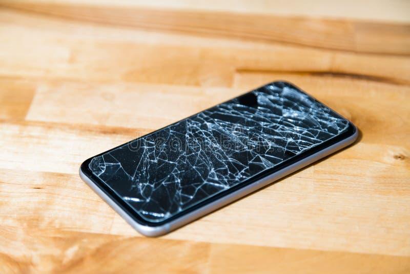 Concept de téléphone intelligent avec l'écran cassé Vue supérieure sur le fond en bois de bureau Écran tactile fendu et brisé d'a image stock