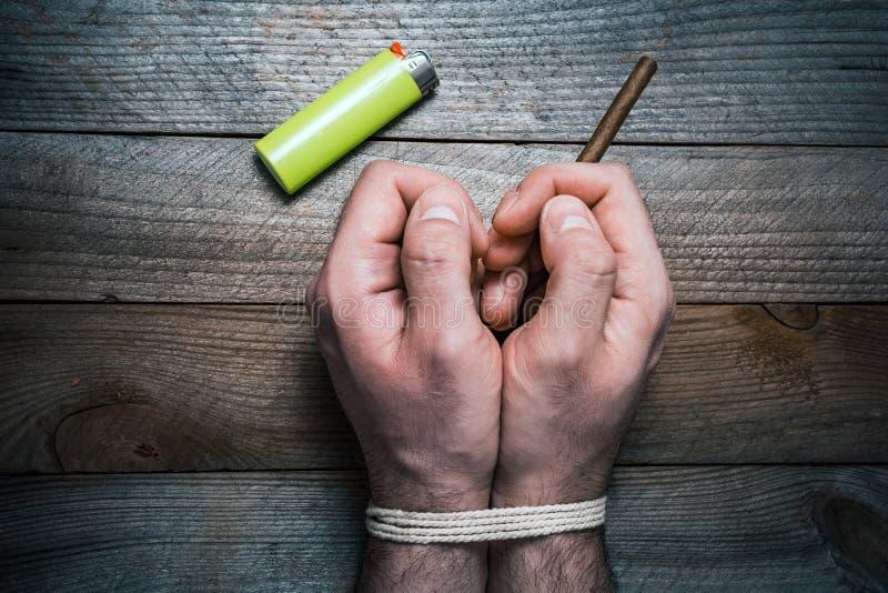 Concept de tabagisme stoppé avec 2 mains attachées sur un Tableau en bois à côté d'un allumeur La main droite tient une cigarette images libres de droits