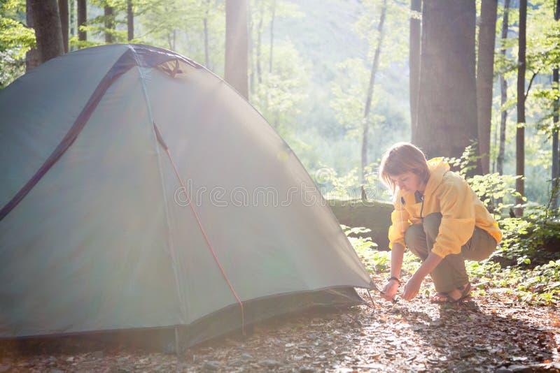 Concept de tourisme Camper et augmenter Tente d'arrangement de femme dans photo stock
