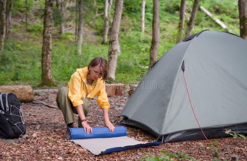 Concept de tourisme Camper et augmenter Tente d'arrangement de femme pendant le jour d'été de forêt photos libres de droits