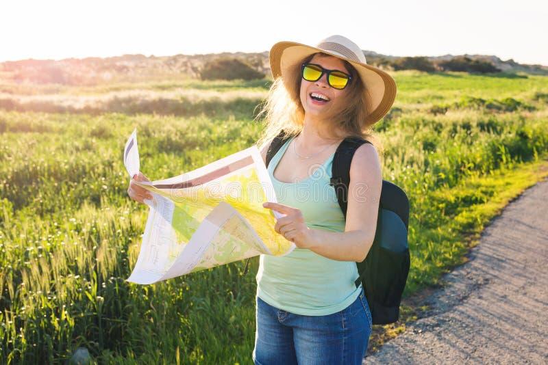 Concept de tourisme, de voyage et d'été - la voyageuse heureuse de femme avec le sac à dos vérifie la carte pour trouver des dire photo stock