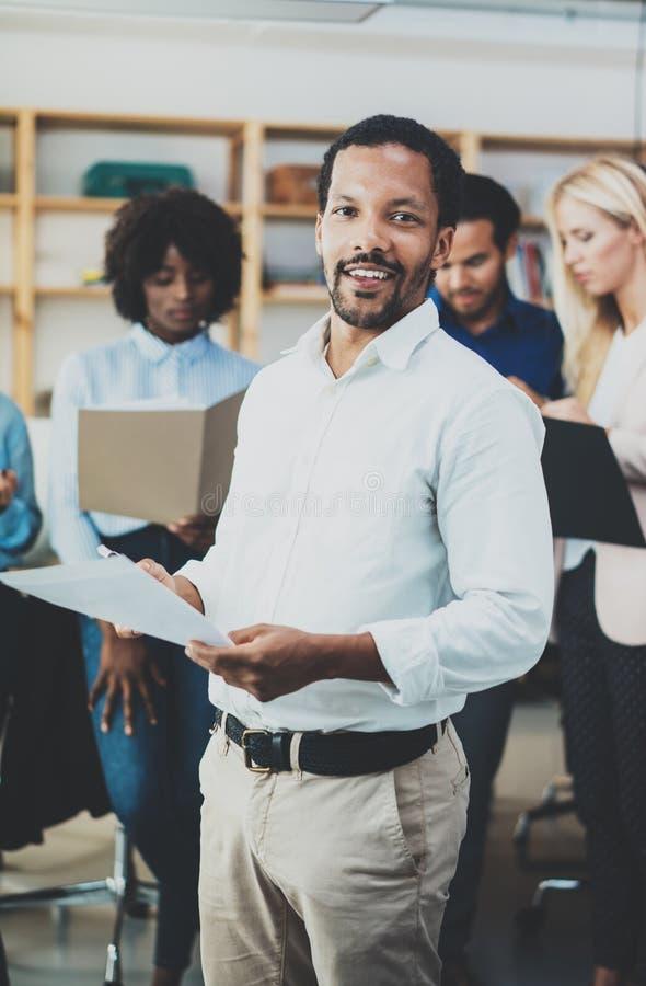 Concept de travail d'équipe dans le bureau moderne Chemise blanche de port de jeune homme d'affaires africain tenant des papiers  image stock