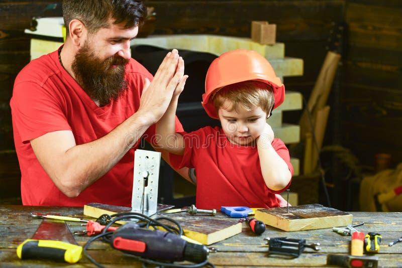 Concept de travail d'équipe Engendrez avec la barbe enseignant le petit fils à utiliser des outils dans la salle de classe, table image libre de droits