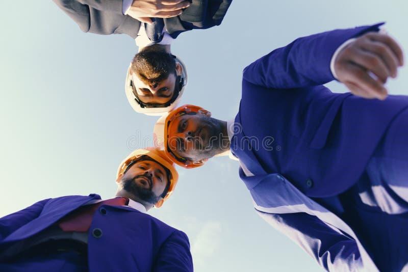 Concept de travail d'équipe et de construction Le conseil des architectes avec les visages sûrs dans les casques regardent vers l photographie stock