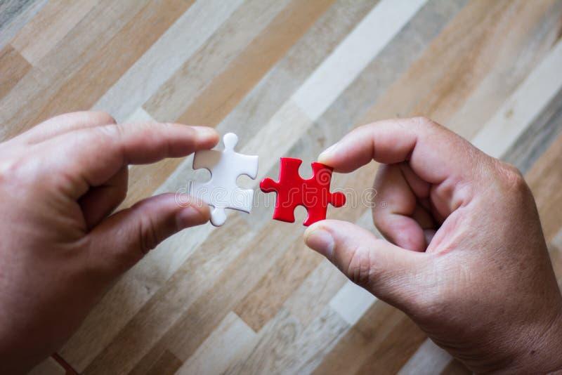 Concept de travail d'équipe utilisant les morceaux blancs et rouges de puzzle photographie stock libre de droits