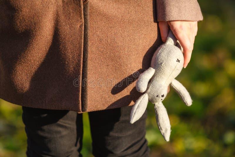 Concept de trouble mental Jeune femme enfantine tenant le rabbin de jouet photographie stock libre de droits