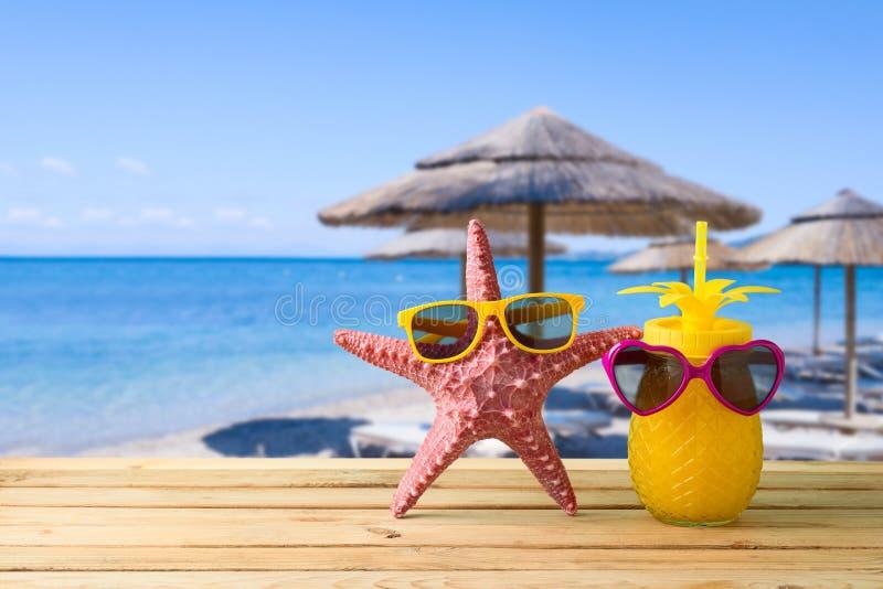 Concept de vacances d'été avec le jus mignon d'étoiles de mer et d'ananas avec des lunettes de soleil au-dessus de fond de plage  photos stock