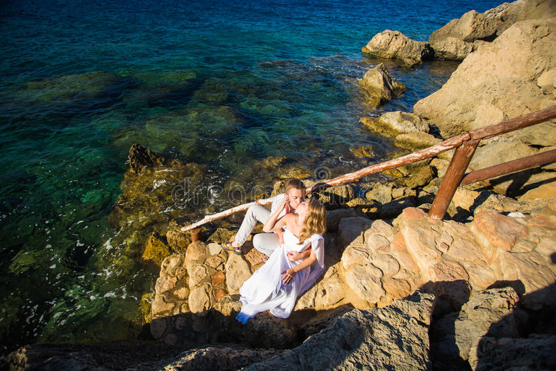 Concept de vacances d'été, de personnes, d'amour et de datation - couple heureux étreignant et embrassant au fond de mer d'été photos stock