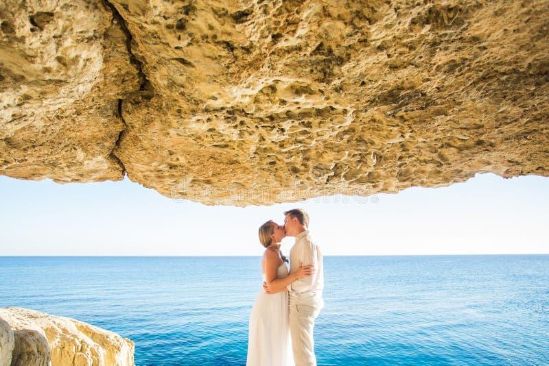 Concept de vacances d'été, de personnes, d'amour et de datation - couple heureux étreignant et embrassant au fond de mer d'été photographie stock libre de droits