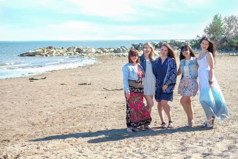 Concept de vacances d'été - le groupe de jeunes femmes de sourire se repose sur le bord de la mer photographie stock libre de droits