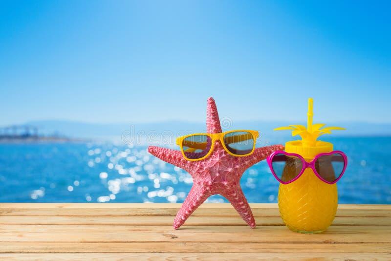 Concept de vacances d'?t? avec le jus mignon d'?toiles de mer et d'ananas avec des lunettes de soleil au-dessus de fond de plage  photos libres de droits